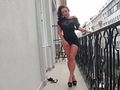 Babe strips on the balcony on a boulevard