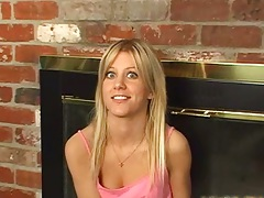 Blonde teen sitting by the fireplace acting naughty in softcore video