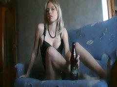 Tee gf sittin gon a couch drinking a bottle