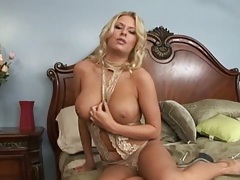 Beautiful milf Riley Evans undresses on the bed